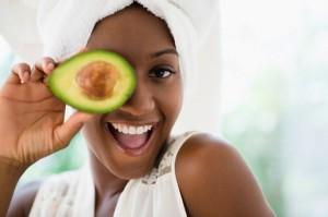 31 Jul 2013, Jersey City, New Jersey, USA --- Black woman holding sliced avocado --- Image by © JGI/Jamie Grill/Blend Images/Corbis